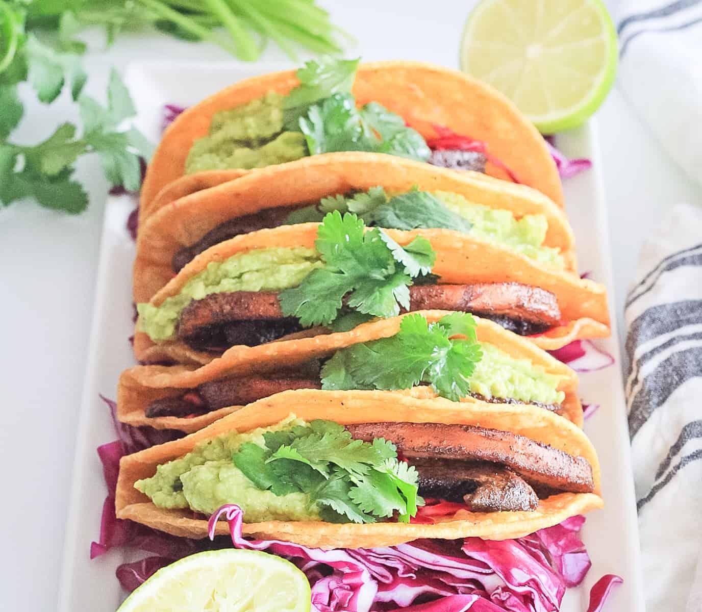 White platter of veggie mushroom tacos in a corn tortilla with guacamole, cabbage and cilantro.