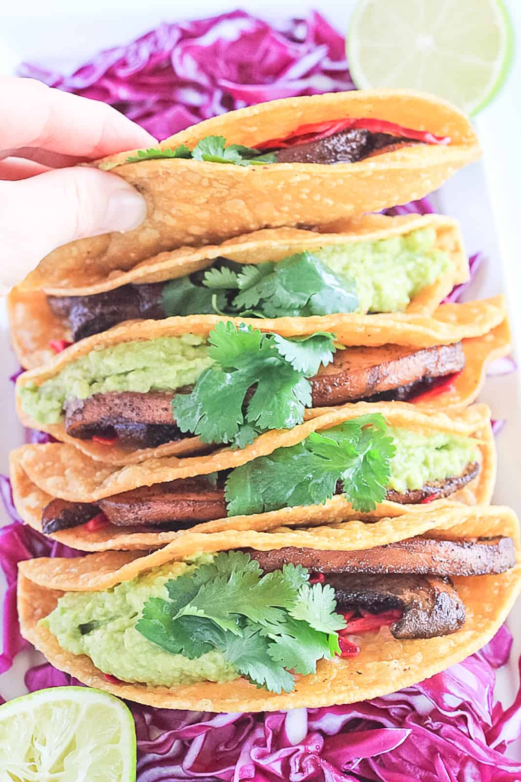 White platter of portobello tacos in a corn tortilla with guacamole, cabbage and cilantro, with a hand picking up a taco.