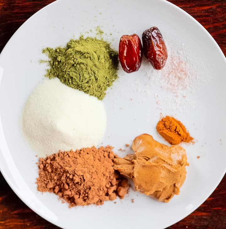 Ingredients for chocolate smoothie: two medjool dates, green superfood powder, collagen, salt, cinnamon, cocoa powder, and nut butter.