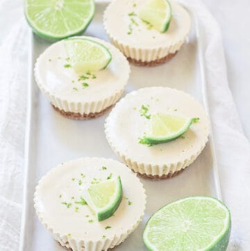 Four lime cheesecakes on a white platter.