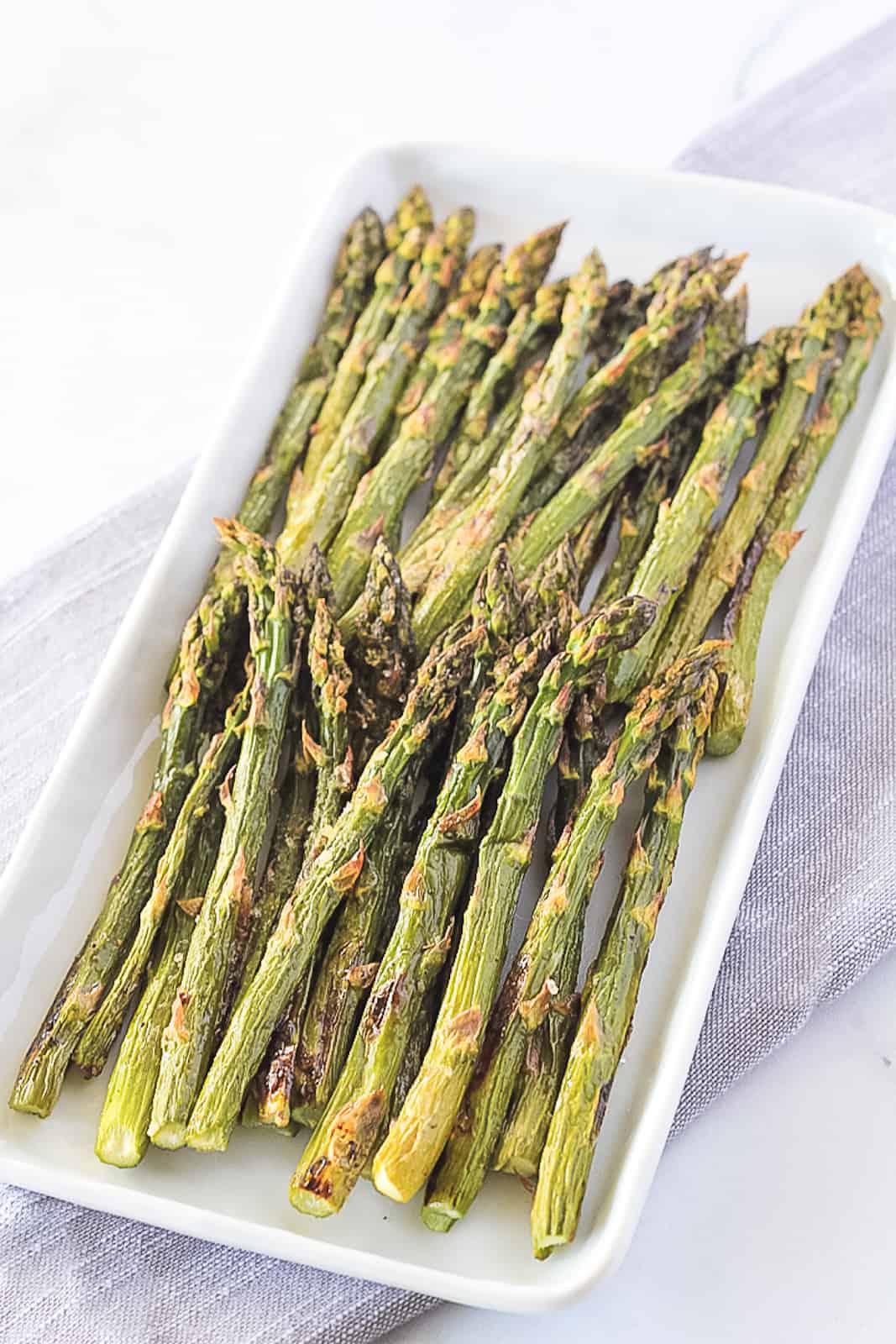 Paleo asparagus stalks on a white serving dish.