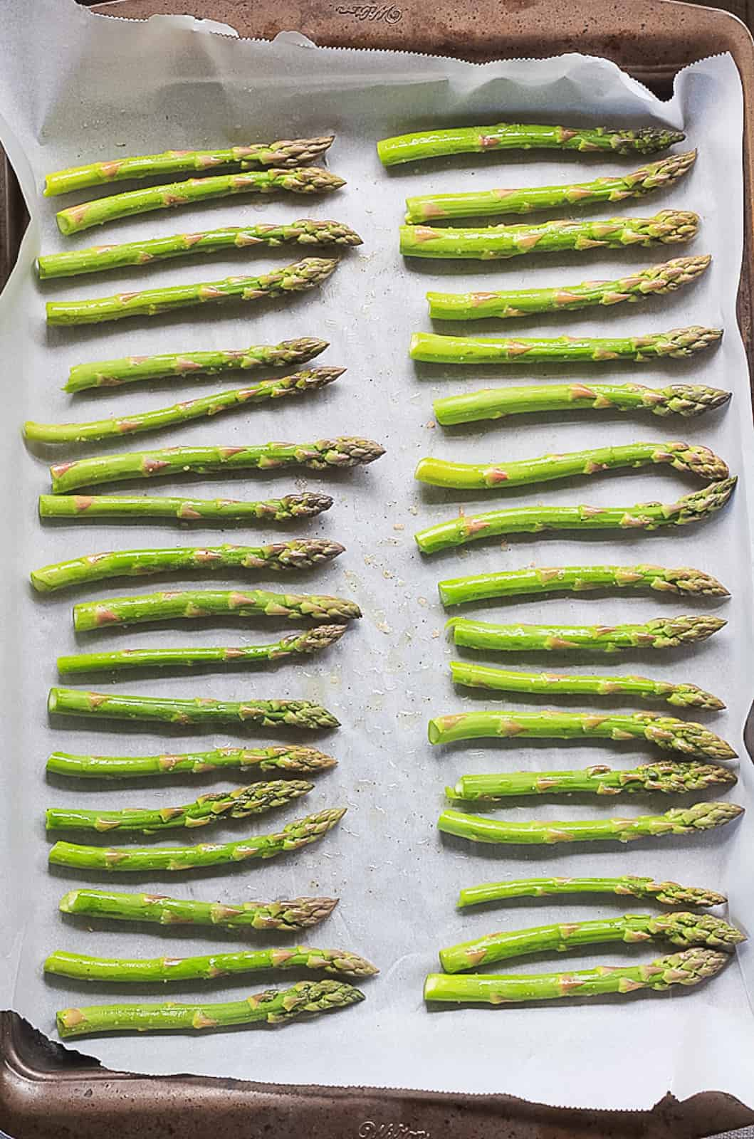Raw asparagus ready for the oven on a parchment paper lined baking sheet.