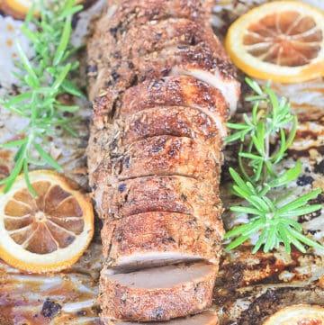 Sliced pork tenderloin on sheet pan with juices, lemon and fresh rosemary.