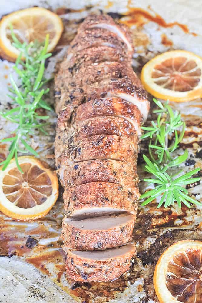 Sliced pork tenderloin on sheet pan with juices, lemon and fresh rosemary.