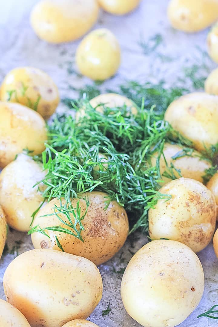 New potatoes on a sheet pan sprinkled with fresh dill and sea salt.