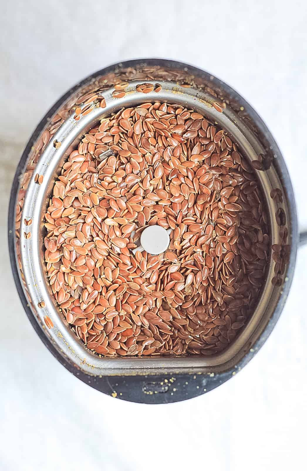 Spice grinder with whole flax seeds in it.