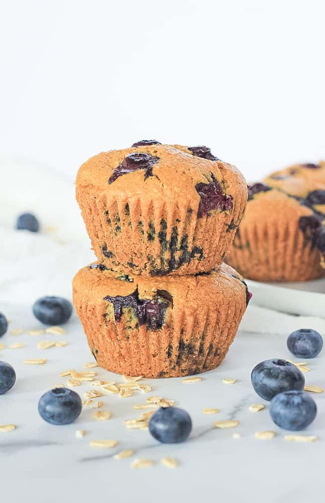 Stack of two blueberry muffins surrounded by a white plate of muffins and fresh blueberries and oats.