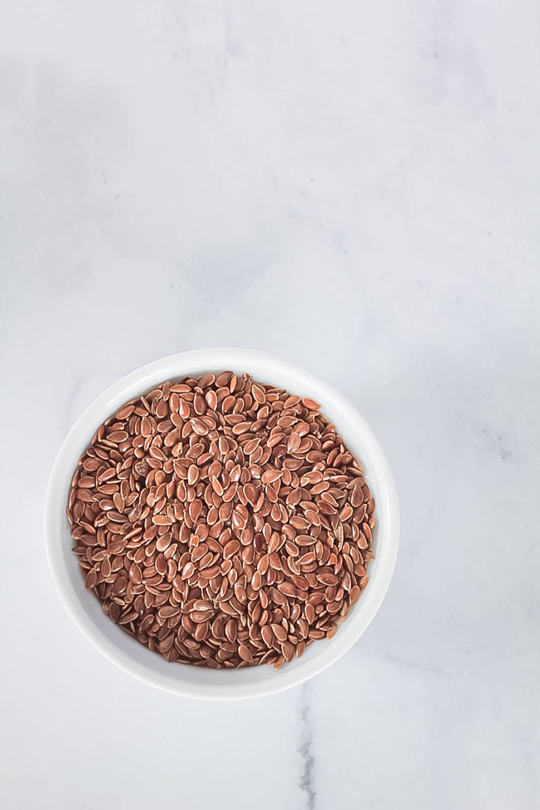 Small white bowl of whole brown flax seeds.