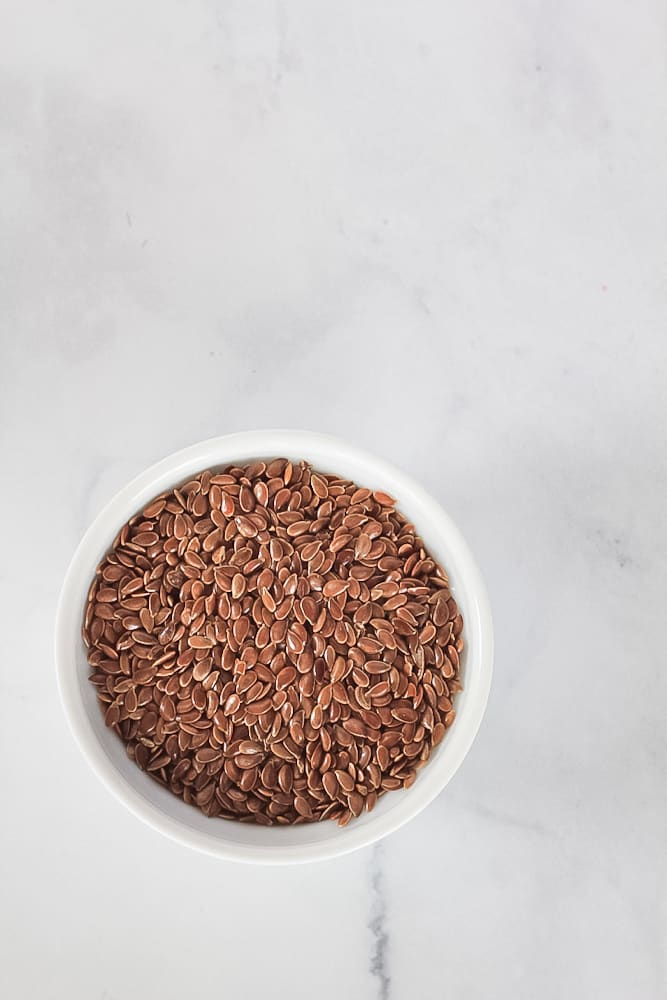White bowl of whole brown flax seeds with flax egg how to recipe.