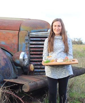 Woman standing in front of antique truck with wooden snack board.