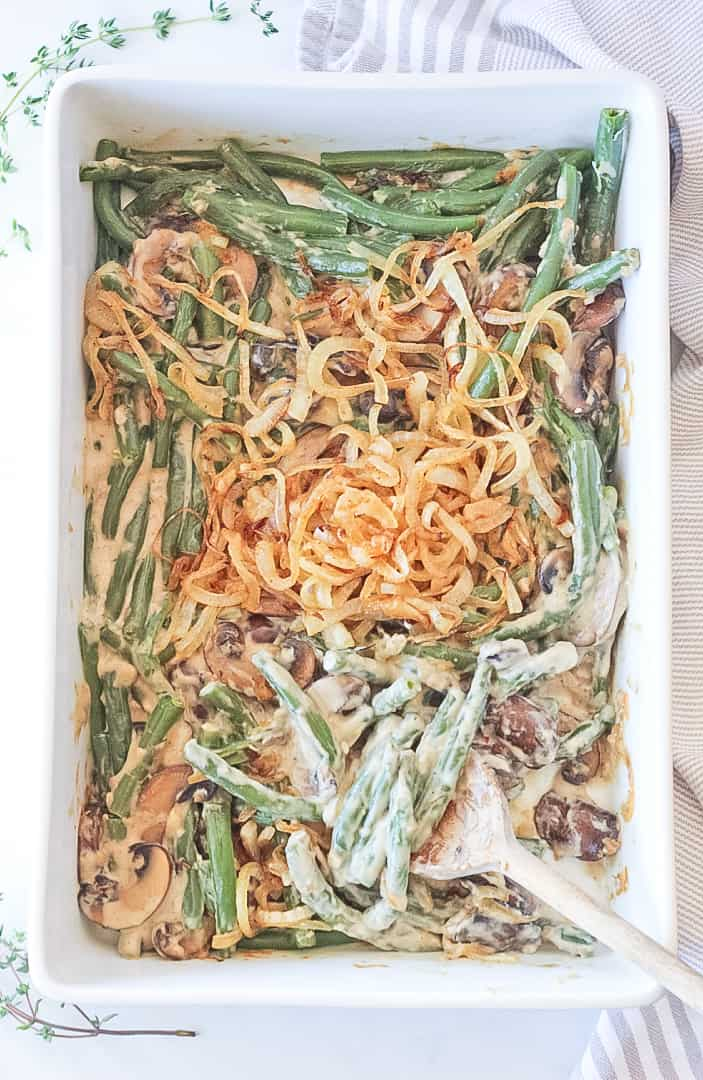 Overhead view of keto green bean casserole with a wooden spoon scooping.