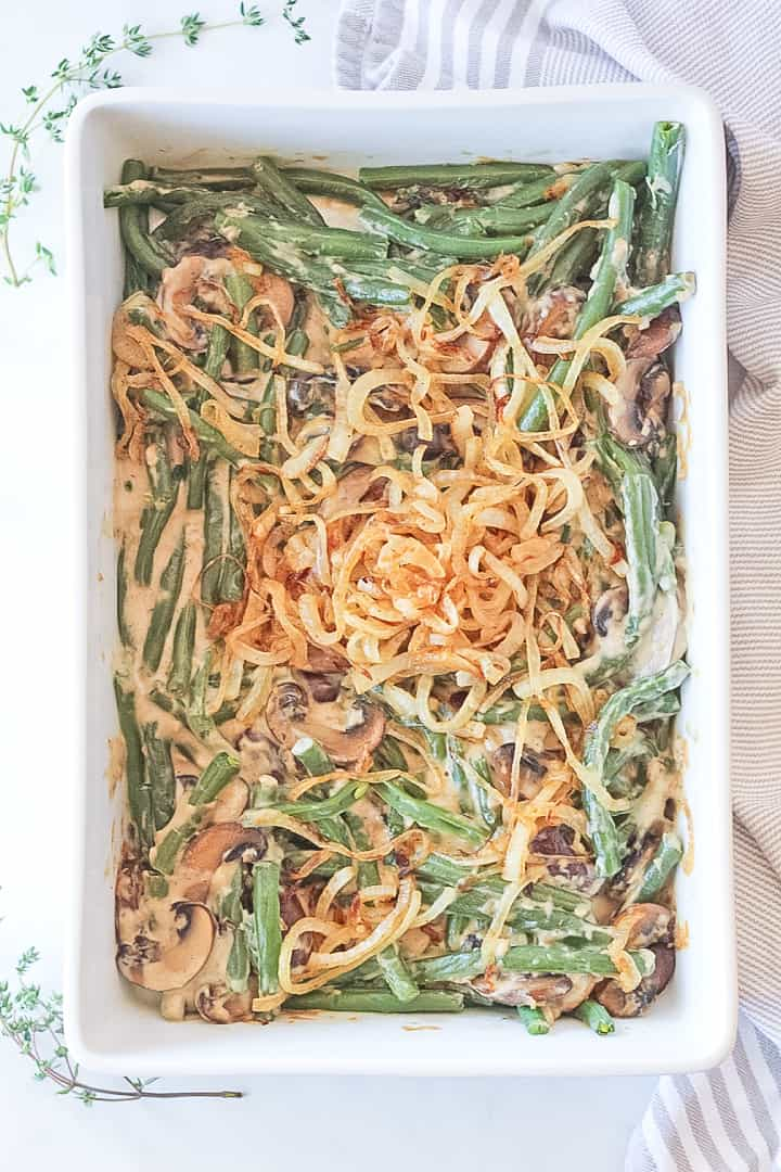 Overhead view of a white baking dish filed with a green bean casserole topped with caramelized onions.