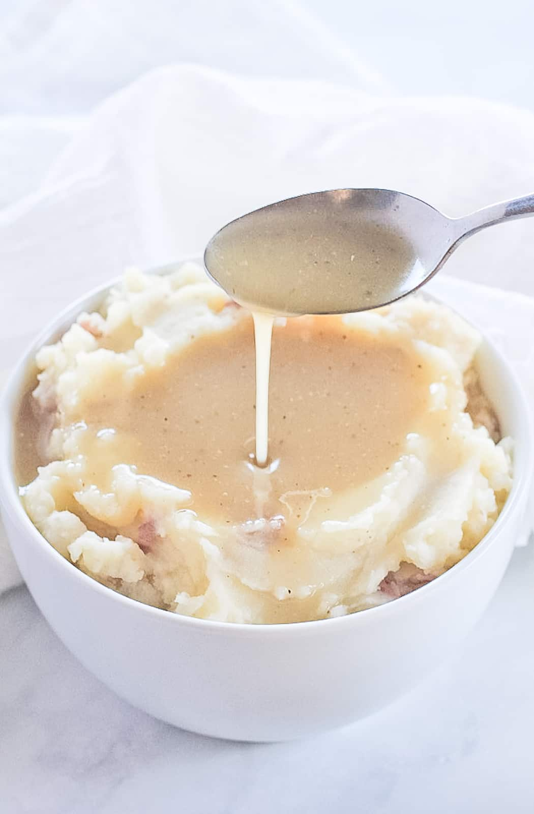 Spoon dipping into a gravy and mashed potato filled bowl.