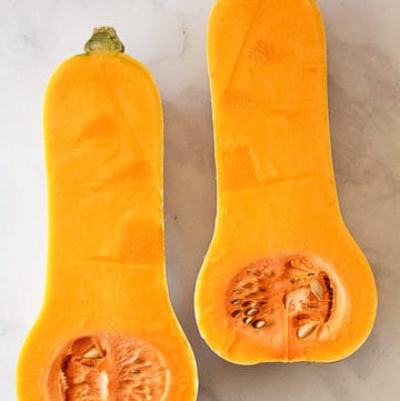 A raw butternut squash cut in half with seeds intact.