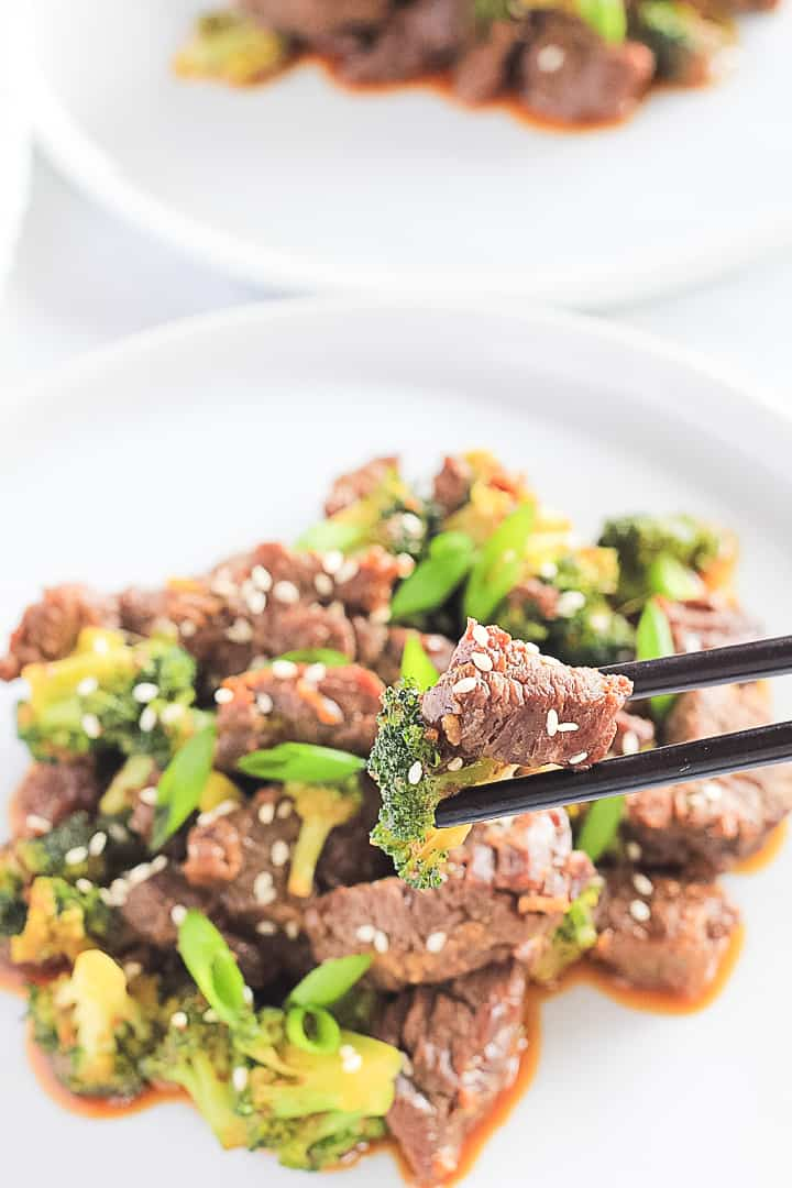 Beef and Broccoli being picked off a white plate with black chopsticks.