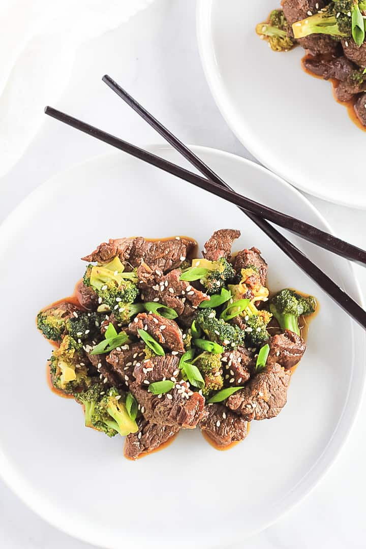 Beef and Broccoli on two white plates with black chopsticks.