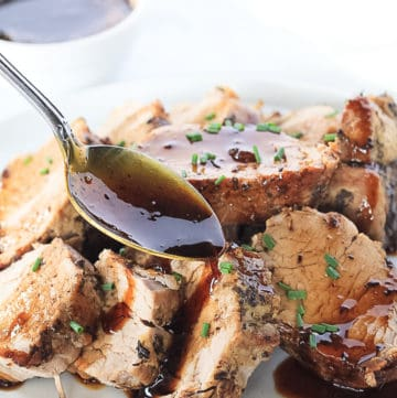 White plate full of sliced pork tenderloin with balsamic glaze being drizzled over top with a spoon and more glaze in a small white bowl.