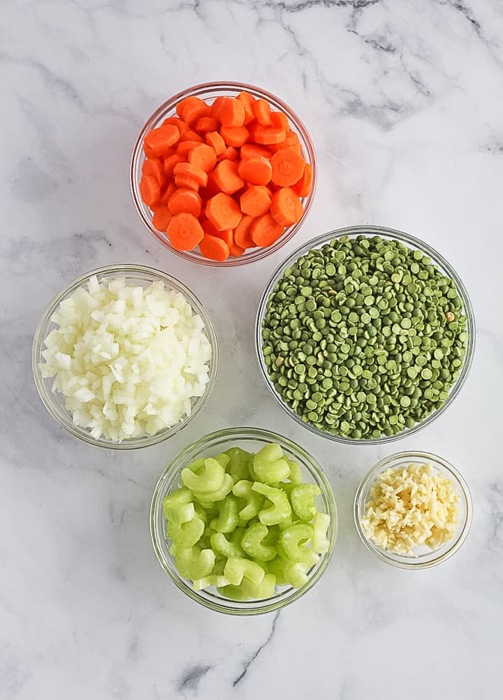 Ingredients for split pea soup include dried split peas, chopped carrots, diced onion, chopped celery and minced garlic each in their own bowl.