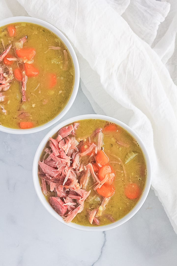 Split pea soup with ham, carrots, celery and onions in two white bowls.