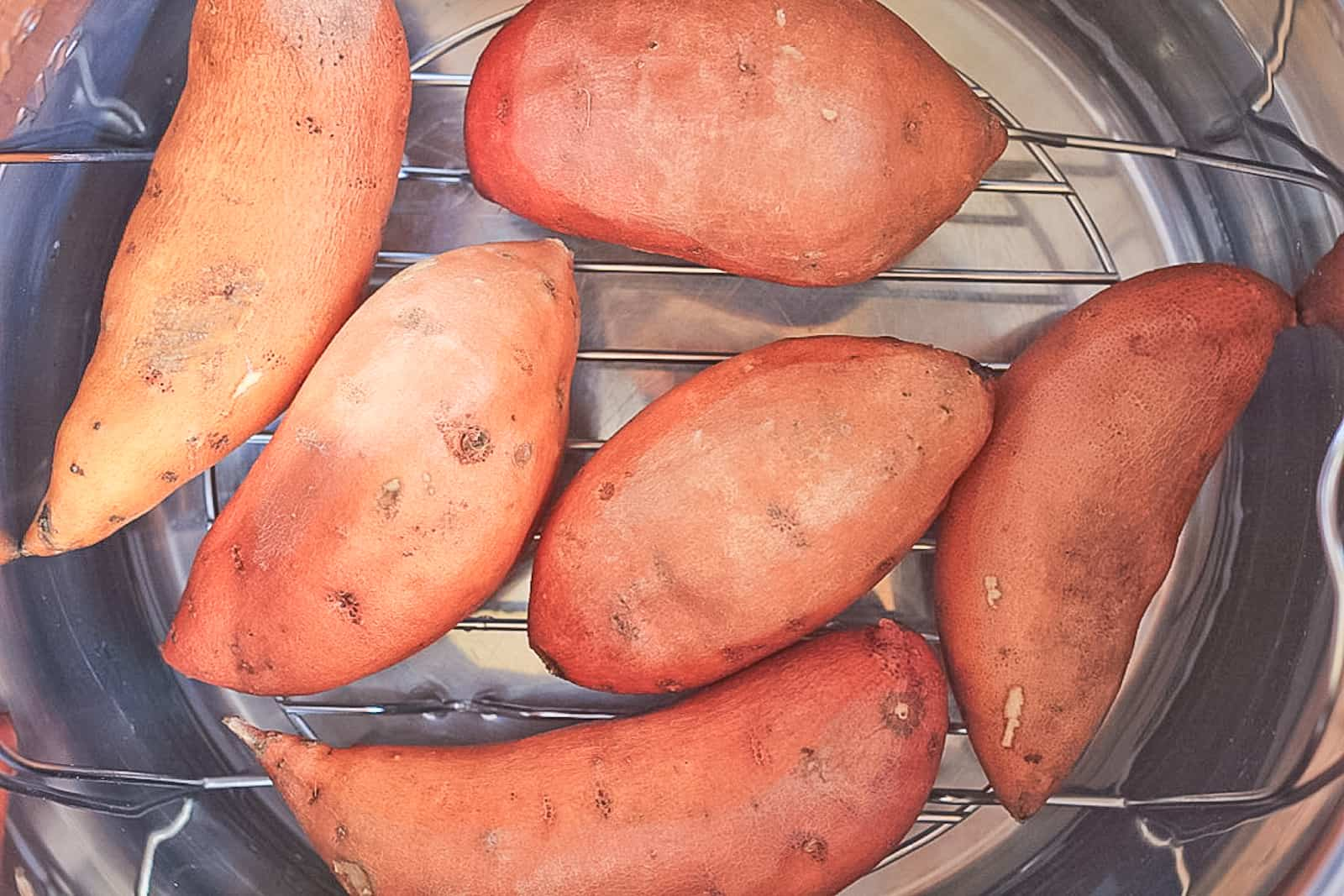 Uncooked sweet potatoes inside the instant pot on the trivet.