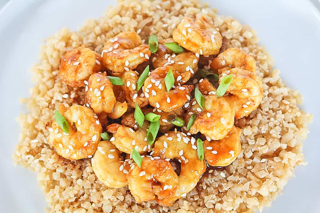 A white plate with orange shrimp over cauliflower rice garnished with sesame seeds and green onions.