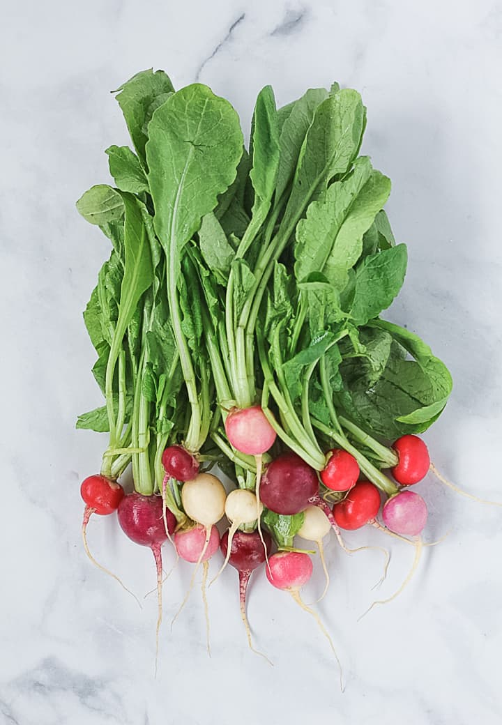 A bunch of fresh raw rainbow radishes with the stems on.