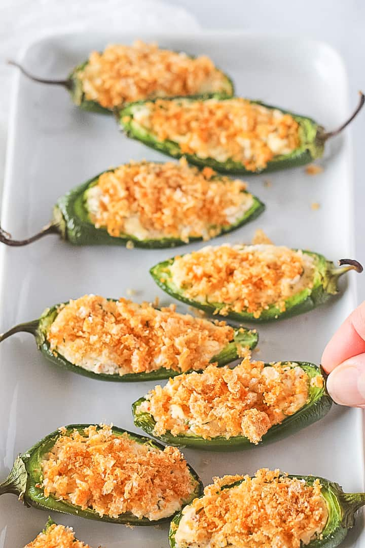 White platter of stuffed jalapeno peppers with a dairy free filling topped with crunchy pork rinds.