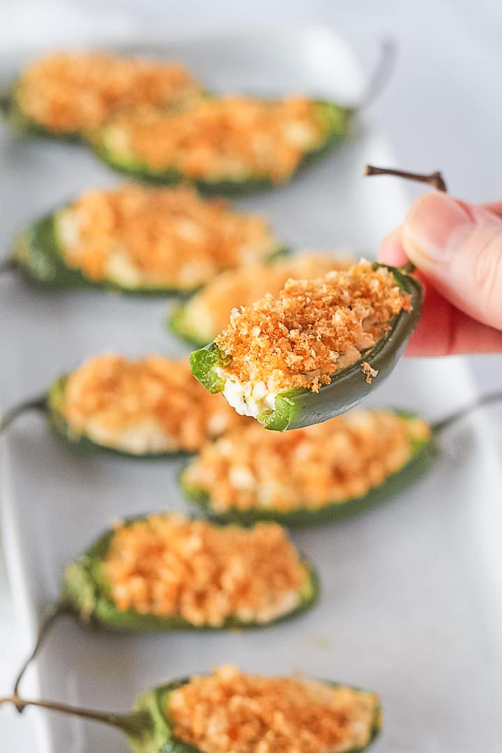 Bite taken out of a stuffed jalapeno popper with a dairy free filling with pork rind topping.