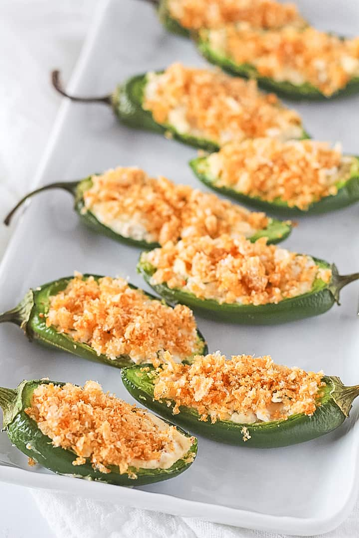 White platter of stuffed jalapeno peppers with a dairy free filling topped with pork rinds.