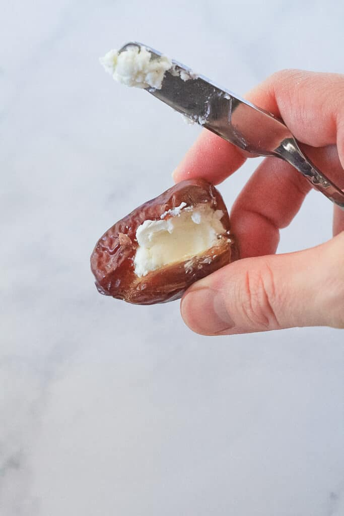 One date being held in hand after being stuffed with goat cheese using a knife.
