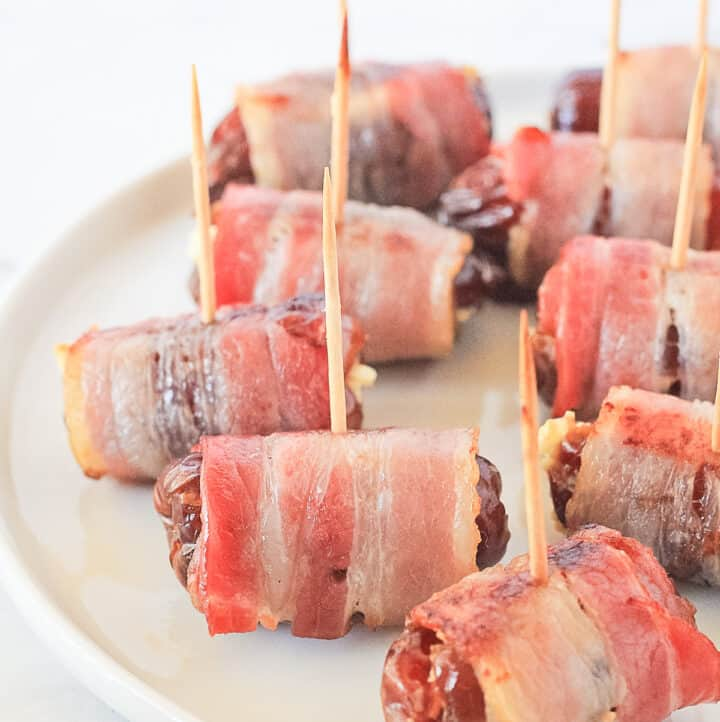 Bacon wrapped dates on a white plate with toothpick sticking out of them.
