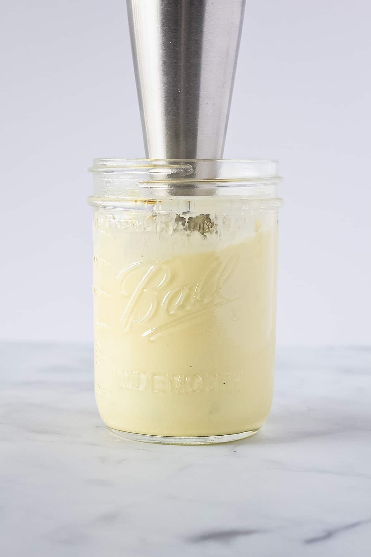 Immersion blender in a pint mason jar with homemade mayo.