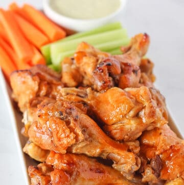 Instant Pot Chicken Wings on a white serving plate with carrots, celery and homemade ranch dressing.