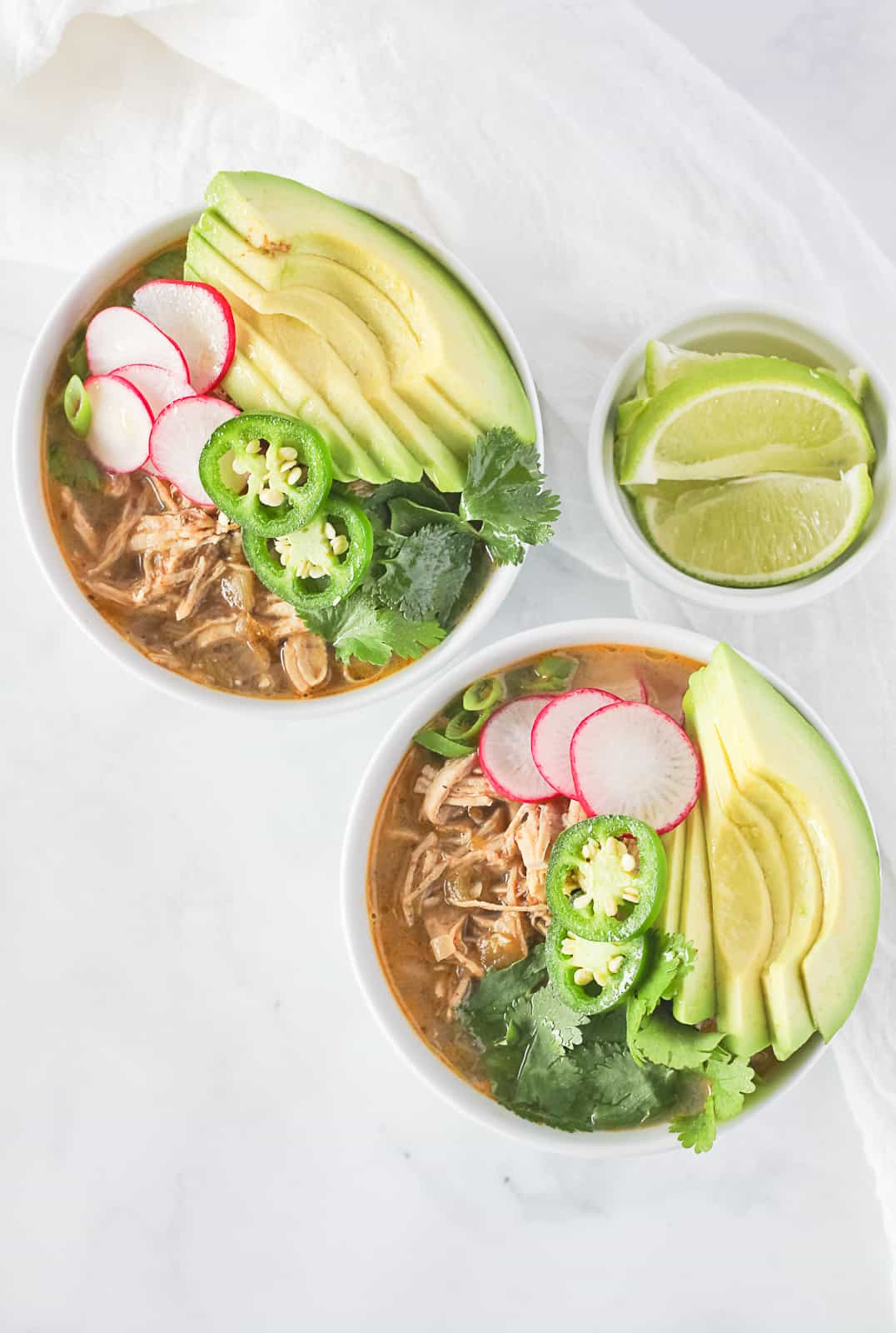 Two white bowls of paleo white chicken chili topped with avocado, cilantro, jalapenos, radishes and green onion.