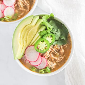A white bowl of paleo white chicken chili topped with avocado, cilantro, jalapenos, radishes and green onion.
