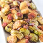 Roasted Brussels Sprouts with bacon on a white serving dish.