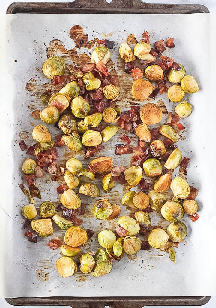 Oven Roasted Brussels Sprouts with bacon on a sheet pan.