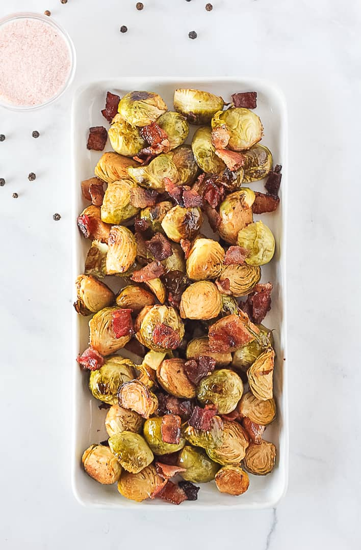 Oven Roasted Brussels Sprouts with bacon on a white serving dish with a small bowl of pink salt.