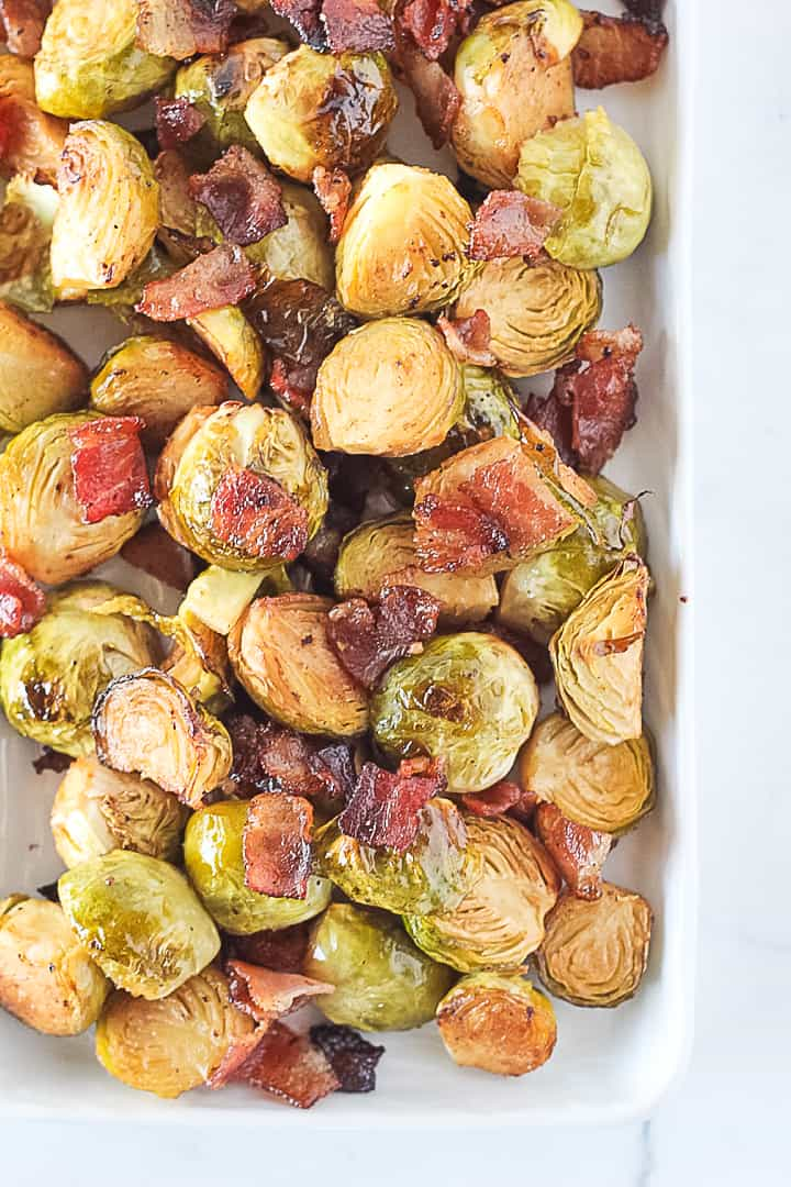 Close up of Oven Roasted Brussels Sprouts with bacon and balsamic on a white serving dish.