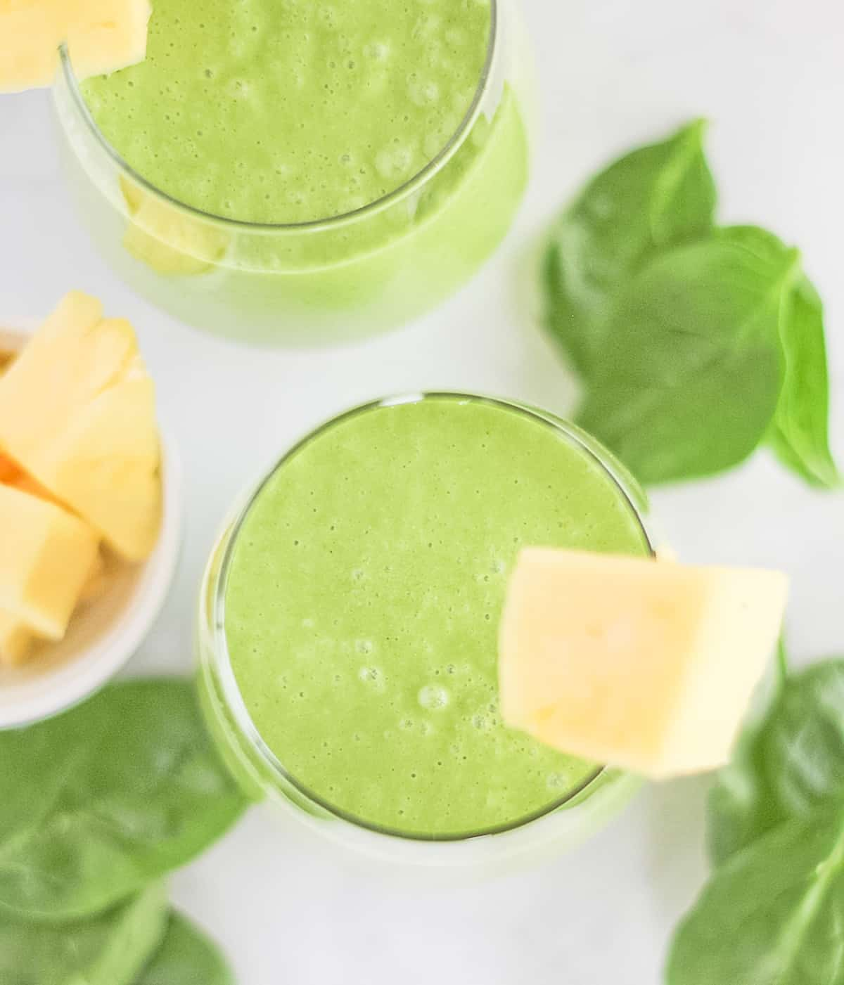 Top view of two glasses filled with pineapple green smoothie surrounded by spinach leaves and chunks of pineapple.
