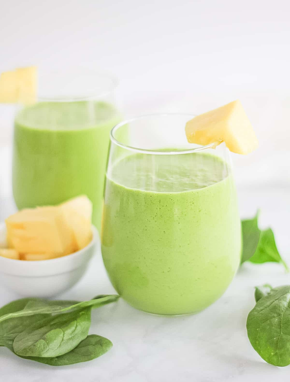 Two glass cups filled with pineapple green smoothie surrounded by spinach leaves and chunks of pineapple.
