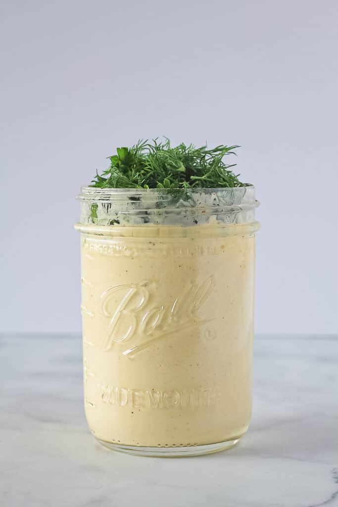 Base of ranch dressing blended in a mason jar with fresh parsley and dill on top before getting mixed in.