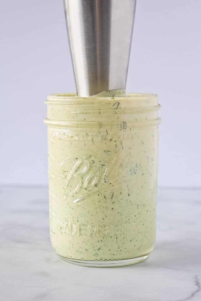Finished homemade ranch dressing in a mason jar with immersion blender in it.