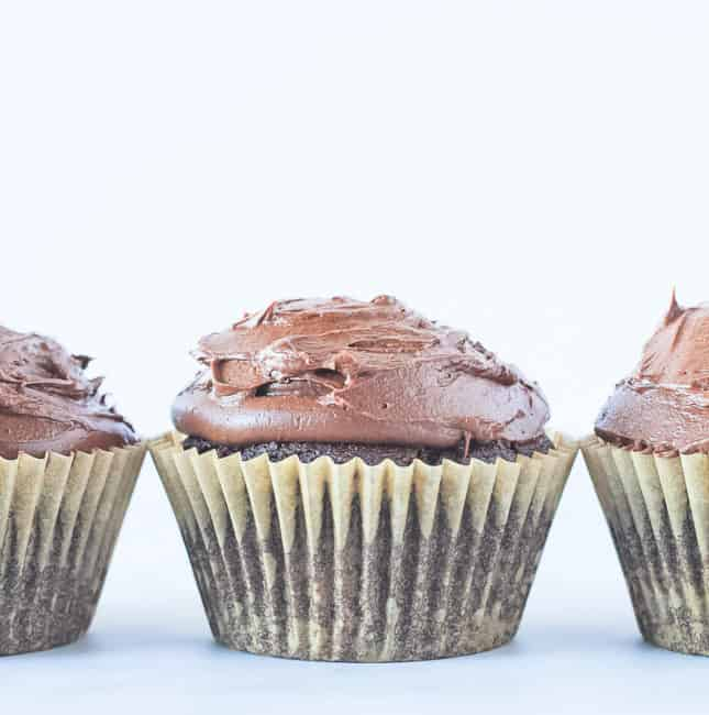 Vegan chocolate cupcakes recipe - three cupcakes in a row topped with chocolate frosting.