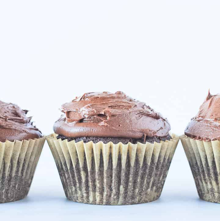 Three vegan chocolate cupcakes in a row topped with chocolate frosting.