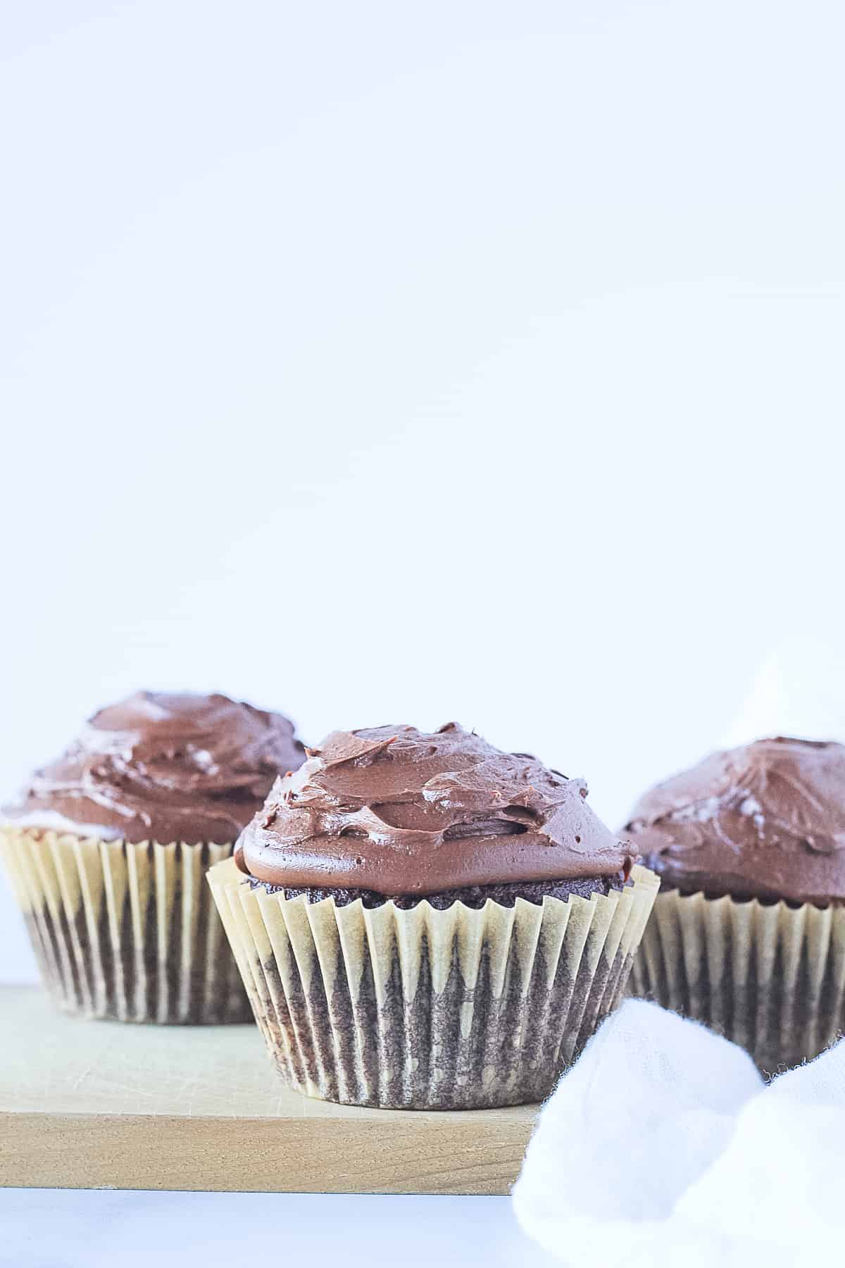 Three Paleo Chocolate Cupcakes topped with chocolate ganache frosting.