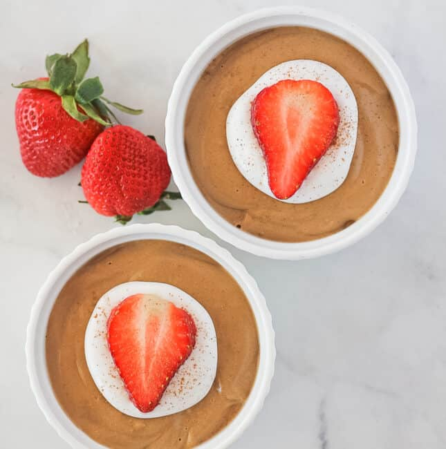 Top view of two white ramekins filled with avocado chocolate mousse topped with coconut cream, cinnamon and a sliced strawberry. With two whole strawberries next to the ramekins.