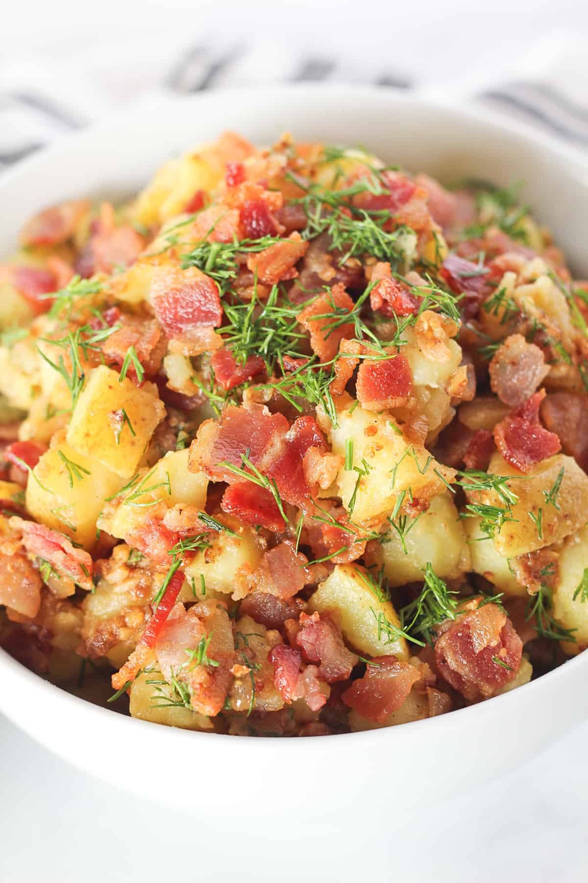 Close up of a white serving bowl filled with Hot German Potato Salad topped with bacon and fresh dill.