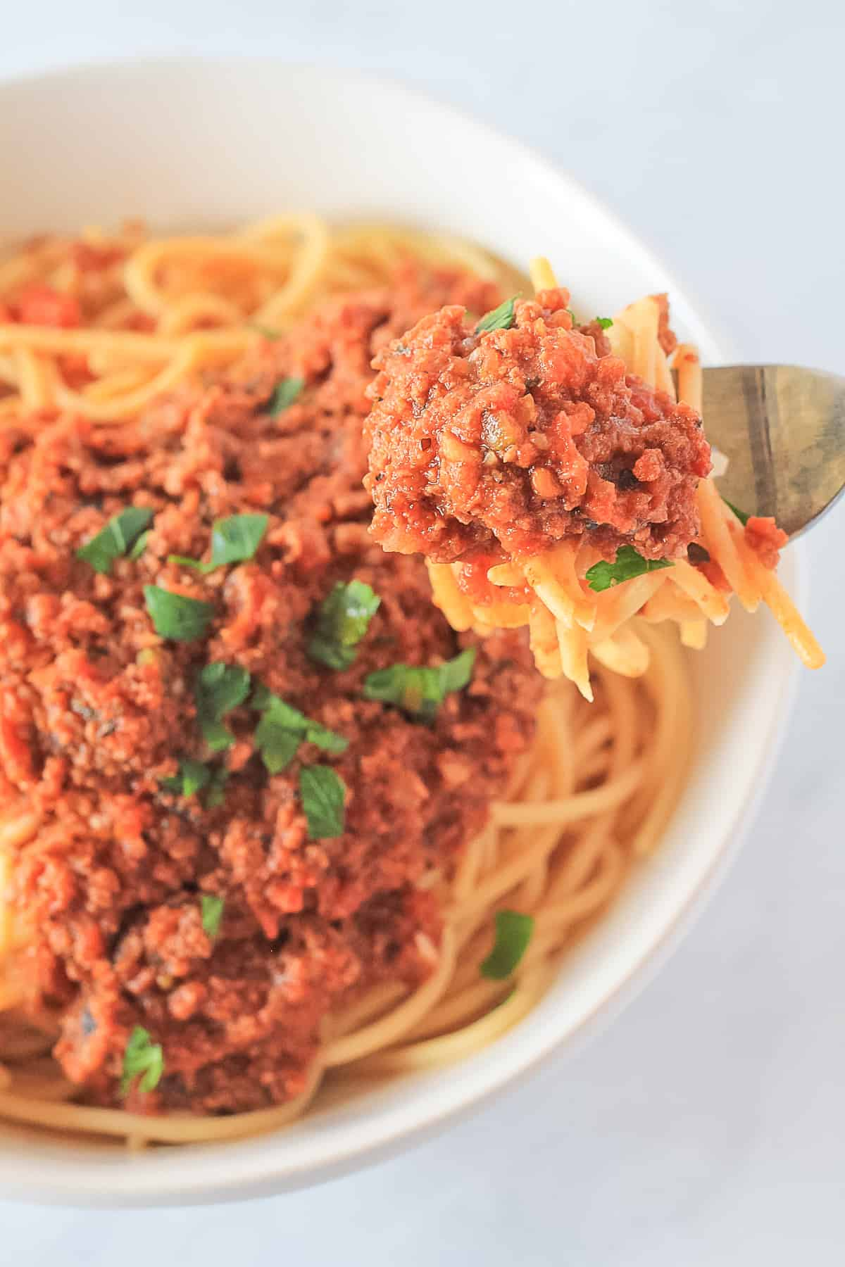 Fork full bite of spaghetti and bolognese pasta sauce.
