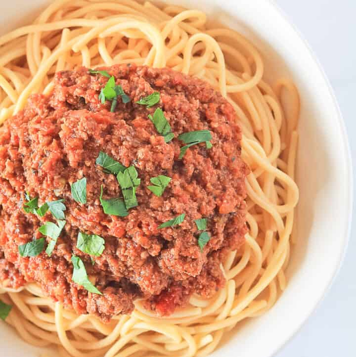 White bowl of spaghetti pasta covered in bolognese tomato meat sauce garnished with fresh parsley.